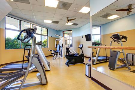 phòng tập thể dục với gương, tv và một số thiết bị tập thể dục