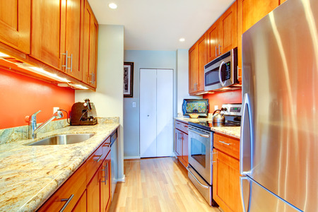 Narrow kitchen room with wooden cabinets, bright orange back splash and granite tops photo
