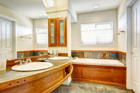 Bathroom with wood and tile trim. View of wooden round counter and large mirror Banco de Imagens