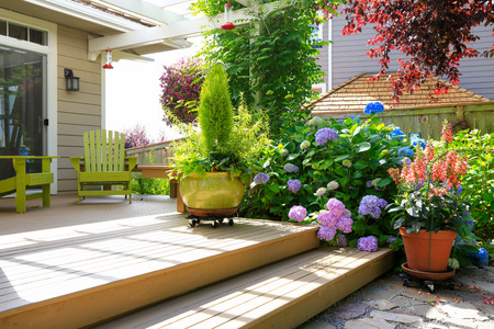 deck chairs: House backyard. View of walkout deck with chairs and flowers Stock Photo