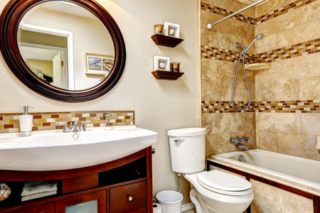 bathroom mirror: Light tones bathroom with tile wall trim. Wooden vanity cabinet with white sink and round mirror Stock Photo