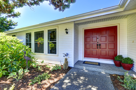 american house: Entrance porch with red door decorated with flower pots