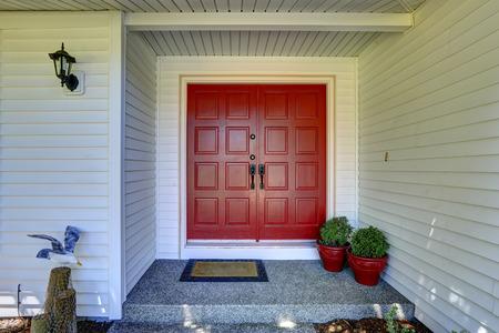 Entree portiek met rode deur versierd met bloempotten