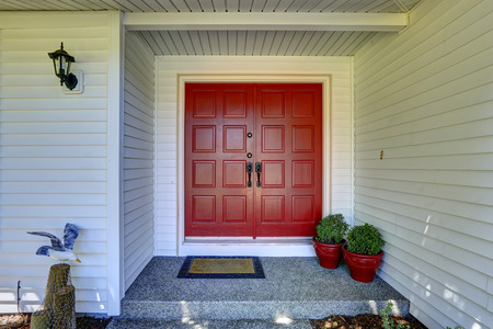 Entrance porch with red door decorated with flower pots