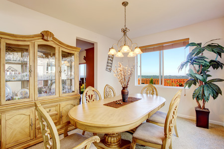 dining table and chairs: Bright dining room with rich carved wood table and chairs, cabinet and palm tree Stock Photo
