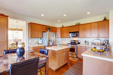 granite kitchen: Kitchen room with granite top dining table, steel appliances and small kitchen island
