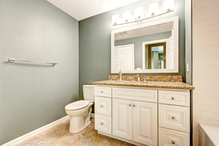 White bathroom vanity cabinet with granite top and mirror. Aqua color walls and beige tile floor photo