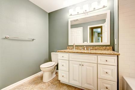 White bathroom vanity cabinet with granite top and mirror. Aqua color walls and beige tile floor photo
