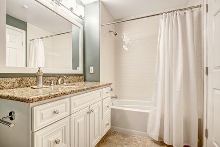 White bathroom vanity cabinet with granite top and mirror. Aqua color walls and beige tile floor