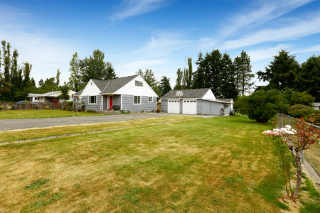 curb appeal: Countryside house exterior. Grey house with garage and driveway