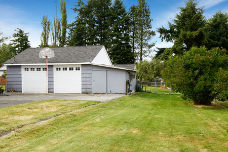two car garage: Countryside real estate. Grey two car garage with driveway Stock Photo