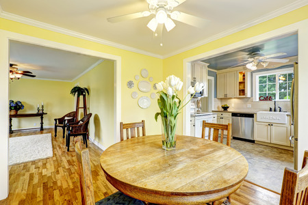 round chairs: Bright yellow dining room with wooden round table and chairs. Beautiful tulips on the table