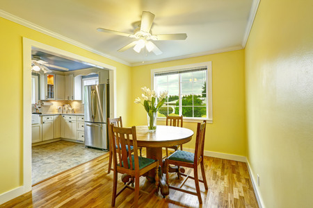 round chairs: Bright yellow dining room with wooden round table and chairs Stock Photo