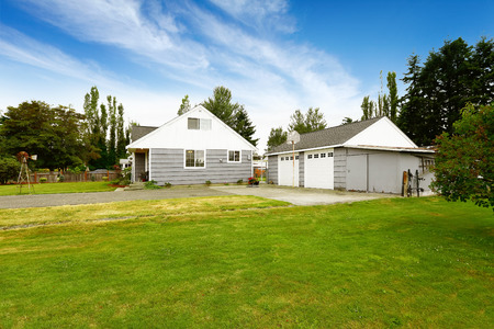 two car garage: Countryside house exterior. Grey house with two car garage and driveway