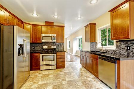 black appliances: Kitchen cabinet with black granite tops and steel appliances and tile back splash trim