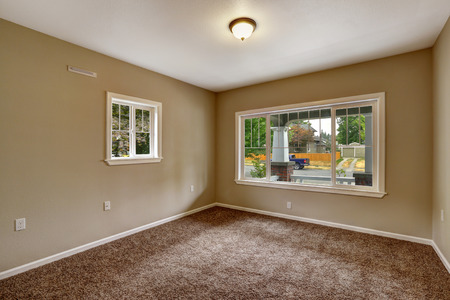 american house: Empty house interior. Bedroom with beige walls, soft brown carpet floor and windows Stock Photo