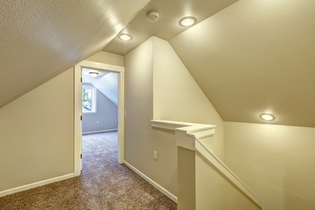 upstairs: Ivory upstairs hallway with carpet floor, vaulted ceiling and staircase Stock Photo