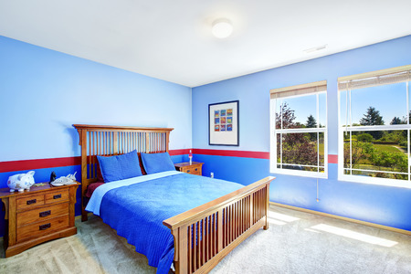 Bedroom interior in bright blue color with red trim. Wooden bed with two nightstands photo