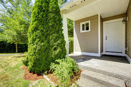 curb appeal: Small entrance porch with stairs and white wooden door Stock Photo