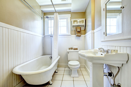 white trim: Claw foot tub in bright bathroom with white wall trim, washbasin stand and toilet