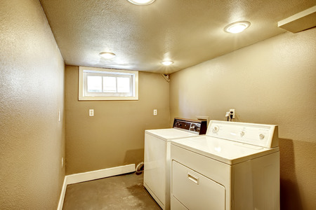 laundry room: Small basement laundry room in beige color. Old laundry appliances Stock Photo