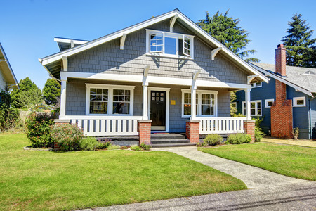 white trim: Clapboard siding house exterior. Large entance porch with brick trim and white railings Stock Photo