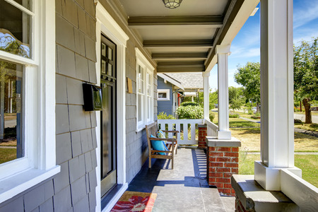 white trim: Clapboard siding house exterior. Large entance porch with brick trim and white railings. Old wooden bench with pillows on the porch