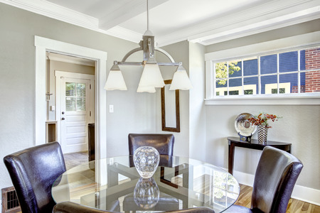 table top: Dining set. Glass round top table with leather chairs. Bright room with windows is perfect for dining area