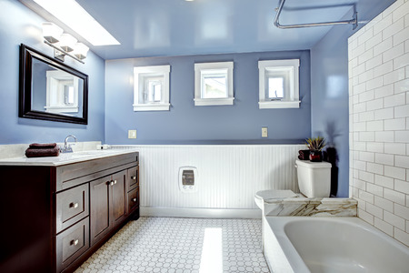 white trim: Beautiful lavender bathroom with white wall trim . Vanity cabinet with drawers and mirror. White bath tub with tile wall trim