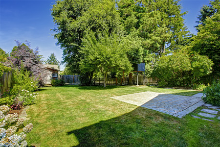 Backyard garden with wooden small fence. Tree house and shed photo