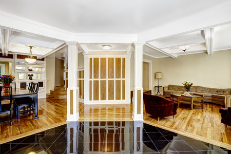 white trim: Luxury interior. Foyer with black shiny tile floor, columns and coffered ceiling system. Brown wall with white trim blend perfectly with hardwood floor