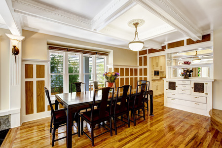 white trim: Luxury spacious dining room with hardwood floor, wood wall trim and coffered ceiling. Room in brown and white tones Stock Photo