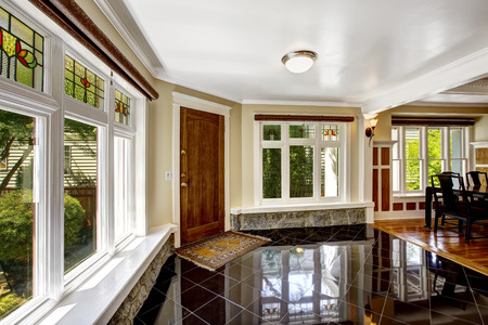 Luxury interior. Foyer with black shiny tile floor, large windows  with stone windowsill base trim photo