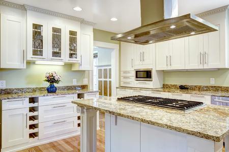 Moderne und praktische Küche Raumgestaltung. Weiß Schrank mit Granitplatten, Kücheninsel mit eingebautem Herd und Stahlhaube Standard-Bild - 31305903