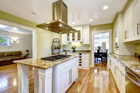 kitchen cabinets: Modern and practical kitchen room design. White cabinet with granite tops, kitchen island with built-in stove and steel hood