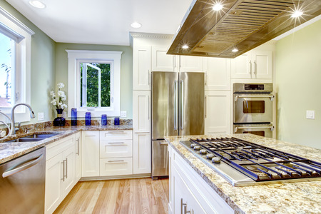 Modern and practical kitchen room design. White cabinet with granite tops and steel appliances, kitchen island with built-in stove and steel hood
