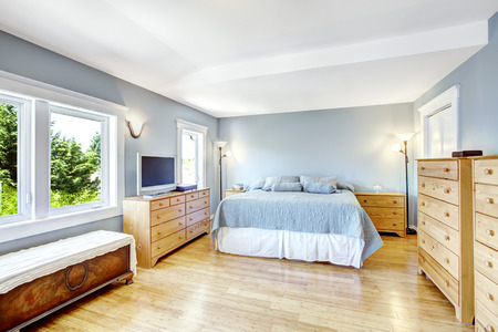Very bright bedroom in light blue tones with wooden furniture set and hardwood floor photo