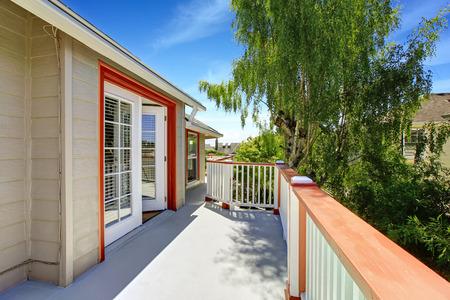 white trim: Wrap-around walkout deck with white railings and orange trim