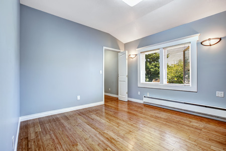 hardwood: Empty bedroom with light blue walls and new hardwood floor Stock Photo