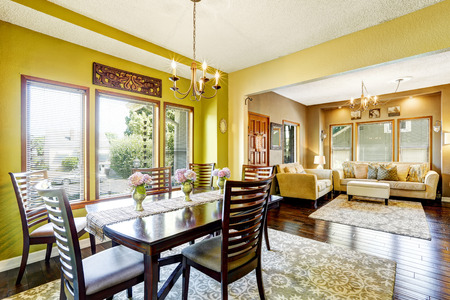 open floor plan: House with open floor plan. Bright yellow dininig room with wooden table set and living room Stock Photo
