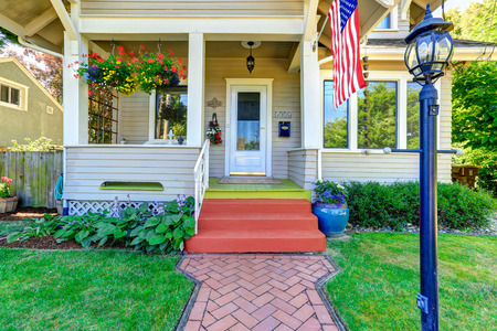 Classic american house entrance porch, decorated with hanging flower pots. Tile brick walkway