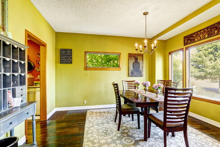 Bright yellow dininig room with wooden table set and antique cabinet