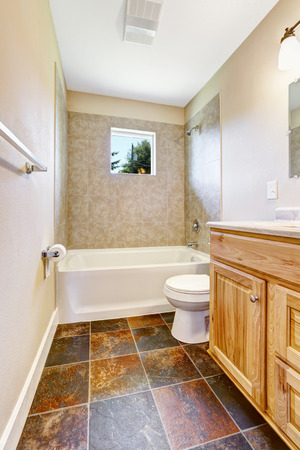 bathroom wall: Empty bathroom with tile wall trim, small window and wooden vanity cabinet. Brown tile floor blend with wooden cabinet Stock Photo
