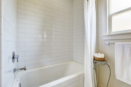 white trim: Simple bathroom with tile wall trim and bath tub, white curtains and stand with wicker basket for towels