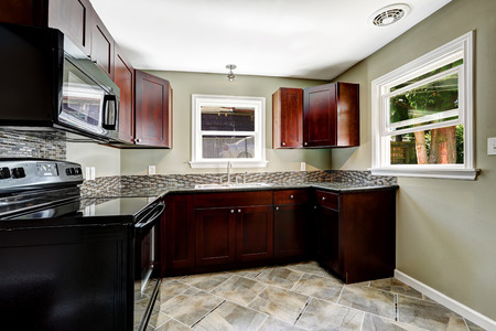 kitchen cabinets: Kitchen with bright burgundy cabinets and black appliances.