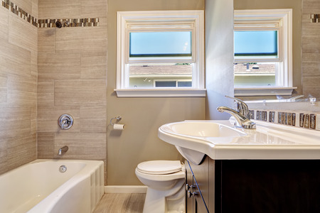 Modern bathroom interior with window and tile wall trim. Empty house interior photo