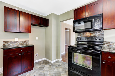 black appliances: Kitchen with bright burgundy cabinets and black appliances. Light mint walls and tile floor