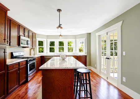 kitchen island: Spacious kitchen room in mint color with french door, bright wooden cabinets and island with stools