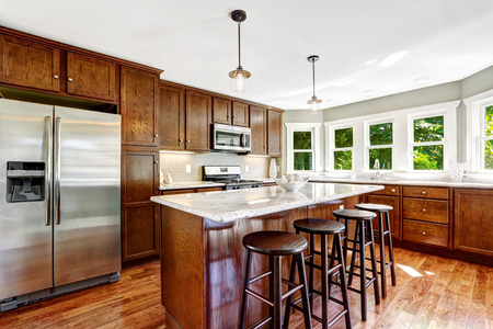 Spacious kitchen room with bright wooden cabinets, marble tops and island with stools photo