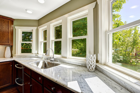 clean window: Beautiful kitchen cabinet with marble top and steel sink Stock Photo